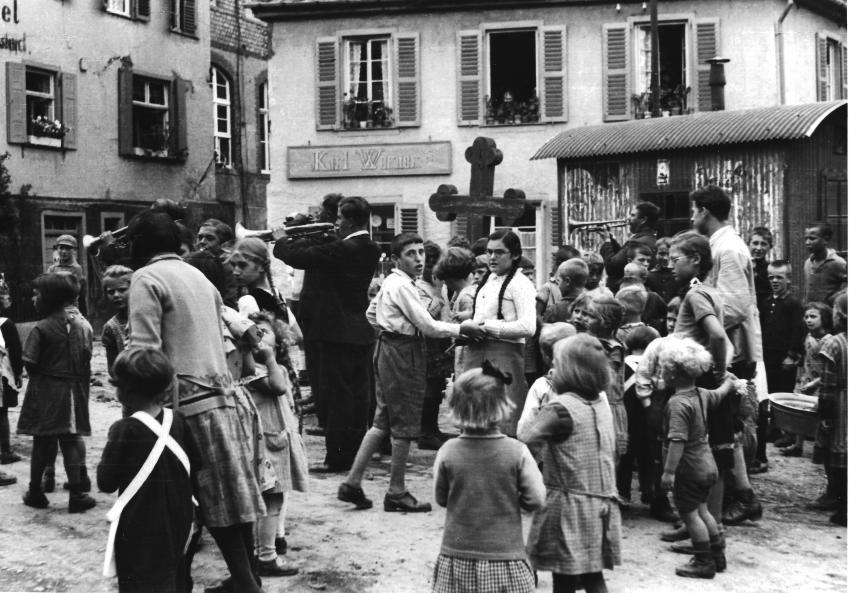Marknadsdag i Rhaunen 1933. Kurt Ermann, i mitten, som bjudit upp en flicka till dans blir överraskad av fotografen. Det här var en central plats i Rhaunen på den tiden, den som tar den här bilden står utanför byns rådhus.