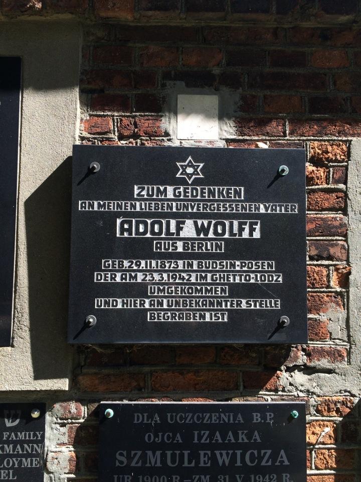 Minnesplakett uppsatt på insidan av muren runt begravningsplatsen